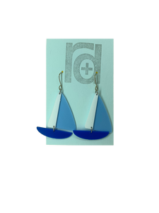 On a light blue earring card are two R+D earrings. They are shaped as sailboats with three pieces: A thin white sail, and larger light blue sail and a classic cobalt blue hull.