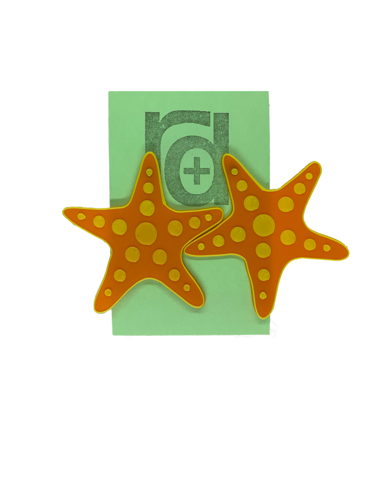 Hanging on a green earring card are two large R+D earrings shaped like star fish. They are orange with a yellow outline and have circle accents across each arm and in the center.