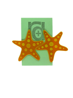 Load image into Gallery viewer, Hanging on a green earring card are two large R+D earrings shaped like star fish. They are orange with a yellow outline and have circle accents across each arm and in the center.