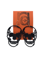 Load image into Gallery viewer, Shown on a orange earring card are two large skull earrings. They are realistic in their shape and are blacked out for the eyes and nose with a jaw that looks like it could be smiling.