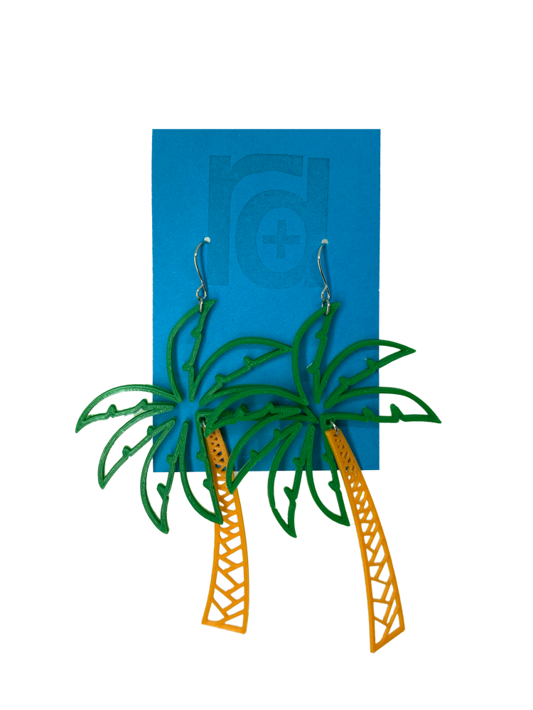 Hanging from a bright blue earring card are two R+D earrings shaped like lush palm trees. They have a wide kelly green fronds above a orange trunk.