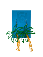 Load image into Gallery viewer, Hanging from a bright blue earring card are two R+D earrings shaped like lush palm trees. They have a wide kelly green fronds above a orange trunk.