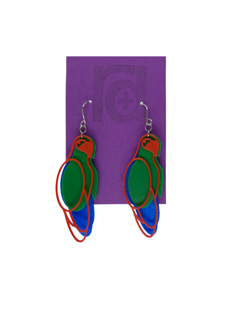 Hanging from a bright purple earring card are two R+D 3D printed earrings. The earrings each have three pieces that form a parrot shape that is red, green, and blue.