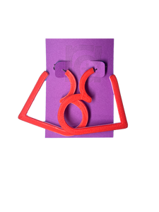 On a purple R+D card is a pair of 3D printed hoops. They are in the shape of a heart with bright red visible on the top layer. Printed with a plant based filament, there are three colors layered: red, white, and  light pink.