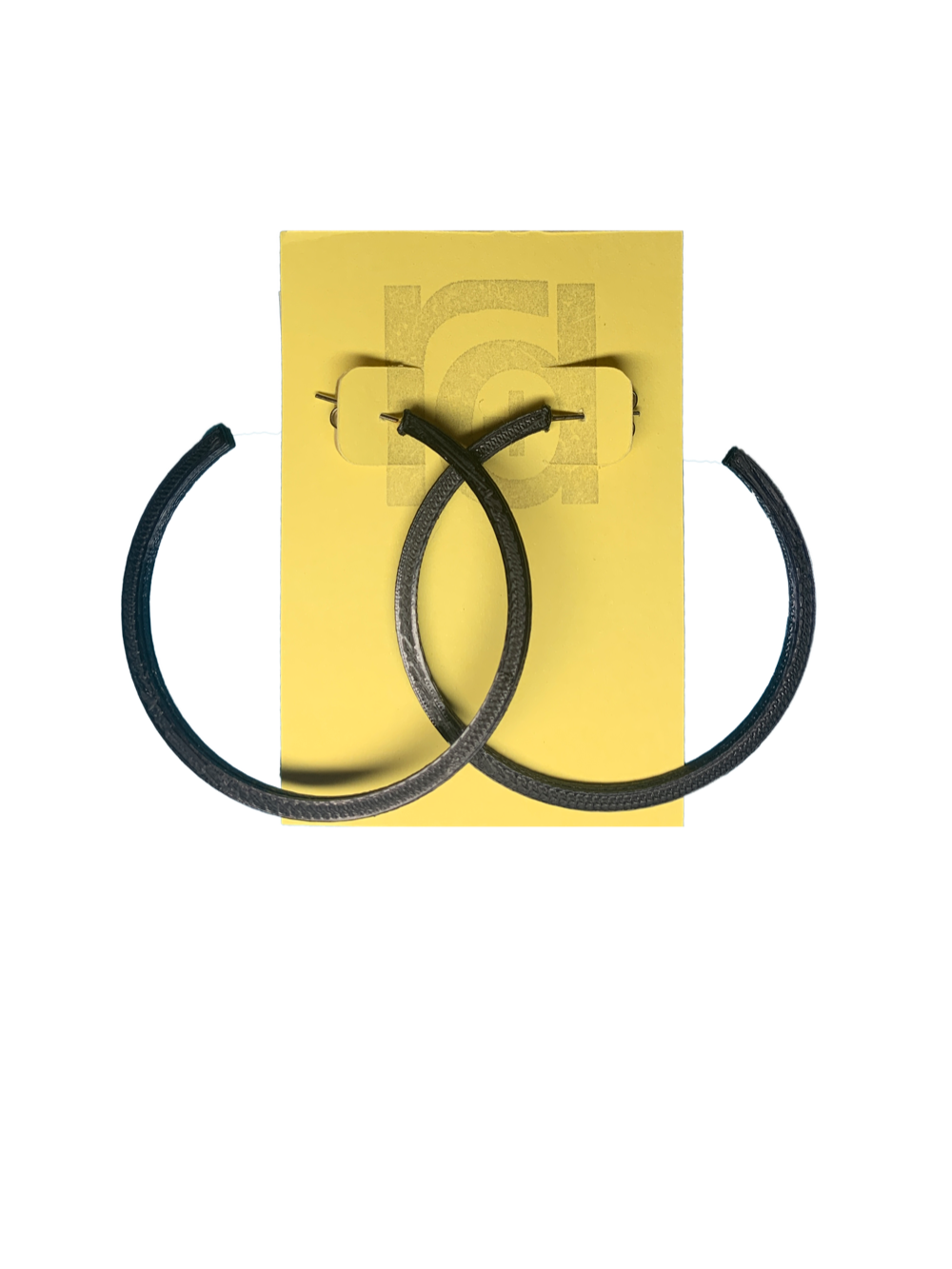 Shown on a yellow R+D card are two 3D printed hoop earrings. They are large two inch hoops in a black that are lightweight and plant based.