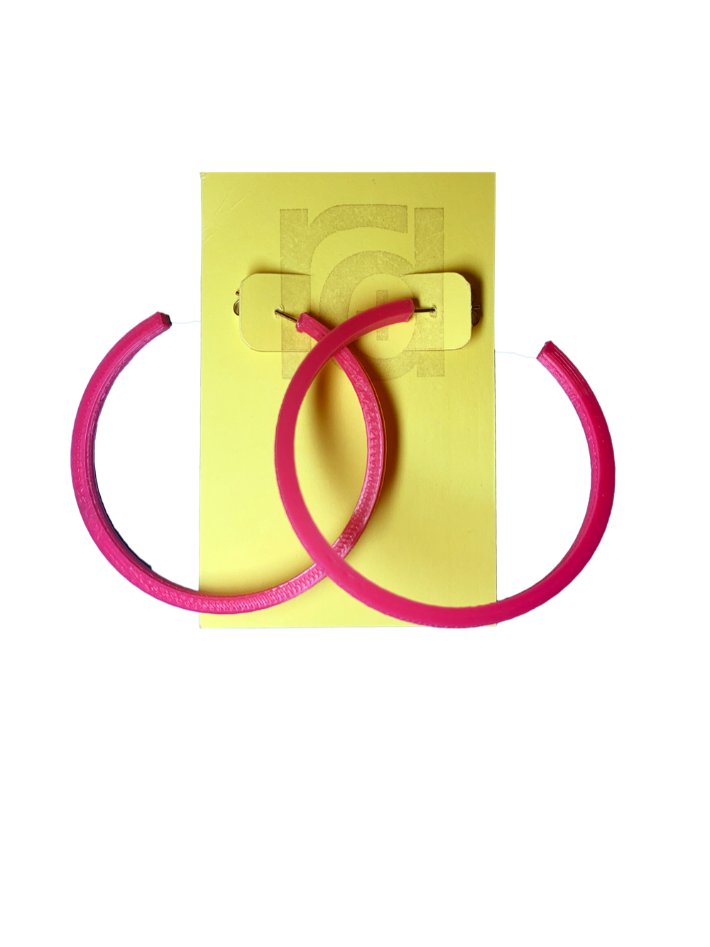Shown on a yellow R+D card are two 3D printed hoop earrings. They are large two inch hoops in a bright hot pink  that are lightweight and plant based.