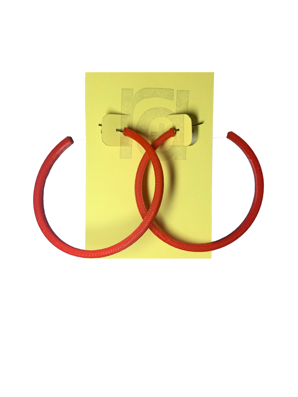 Shown on a yellow R+D card are two 3D printed hoop earrings. They are large two inch hoops in a bright red that are lightweight and plant based.