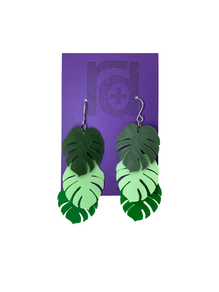 Hanging from a purple earring card are two R+D earrings. The earrings have three monstera frond leaves that hang at different levels. They are also each different color: Olive green, Mint green, and kelly green.