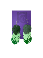 Load image into Gallery viewer, Hanging from a purple earring card are two R+D earrings. The earrings have three monstera frond leaves that hang at different levels. They are also each different color: Olive green, Mint green, and kelly green.