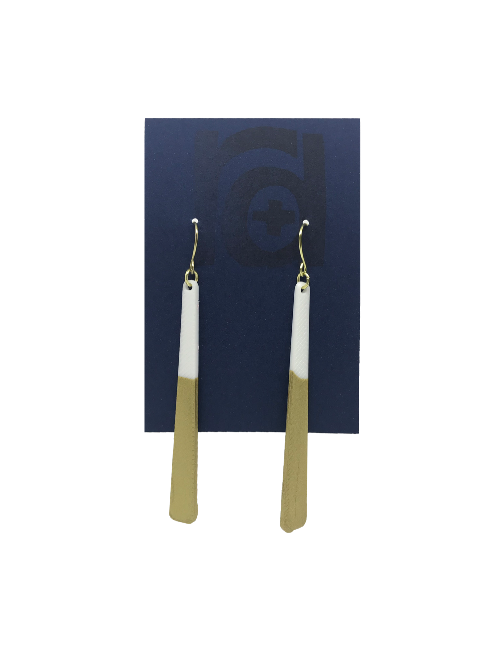 Shown on a sustainable dark blue earring card, these earrings are long dangles that flare out slightly. The white plant based earring is dipped into metallic gold paint to give a perfect shimmering accent.