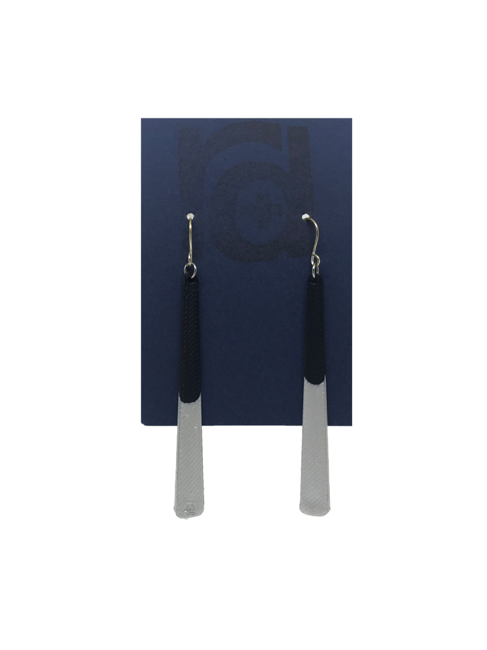 Shown on a sustainable dark blue earring card, these earrings are long dangles that flare out slightly. The black plant based earring is dipped into metallic silver paint to give a perfect shimmering accent.