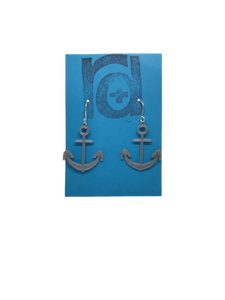 Two earrings hang on a blue earring card. The earrings are 3D printed in a plant based silver filament. They are shaped like anchors.
