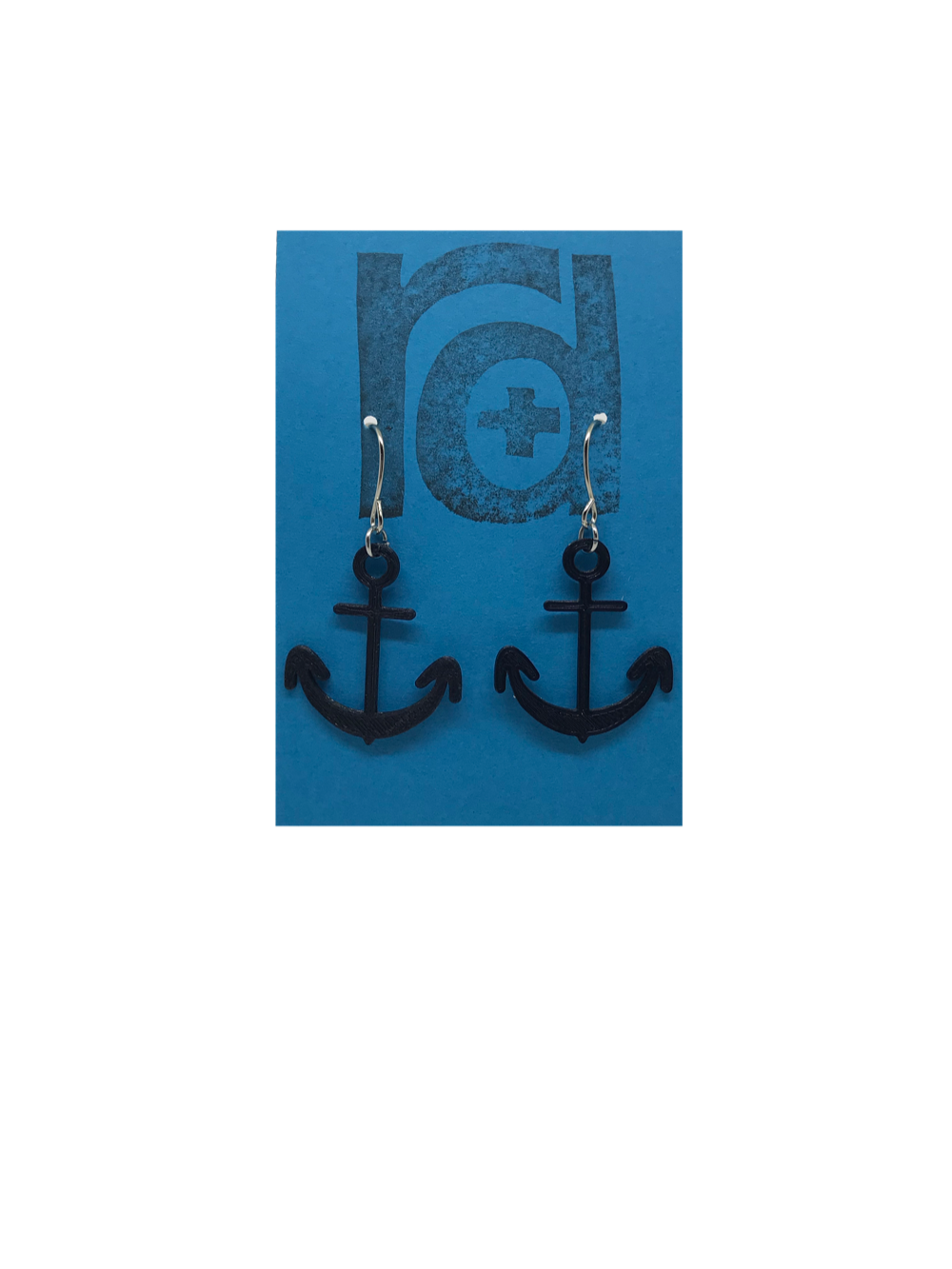 Two earrings hang on a blue earring card. The earrings are 3D printed in a plant based black filament. They are shaped like anchors.