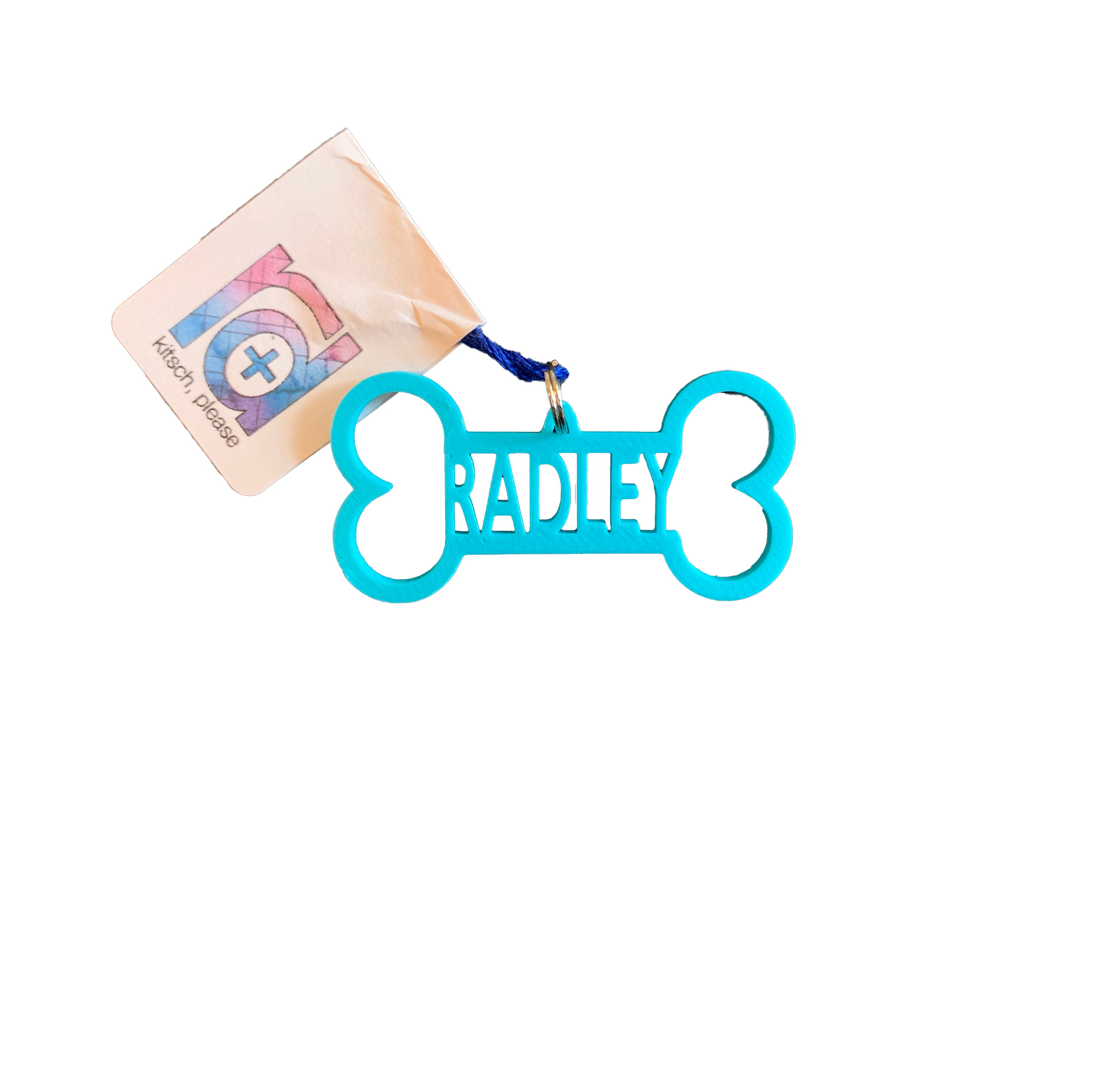 A bright teal dog bone tag is pictured. It is 3D printed and has the name Radley in the center. It can be customized to any pet name and to 15 other colors.