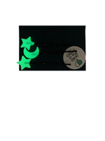Load image into Gallery viewer, Shown on a dark navy blue paper card are three bobby pins with 3D Printed pieces attached to the ends. There are two shape like stars and one shaped like a cresent moon. They glow in the dark; here they are shown in the glowing green color they appear after being charged and brought to a dark place.