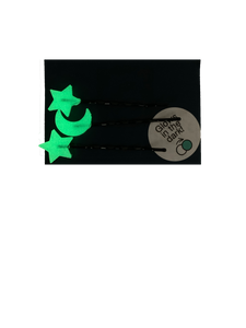Shown on a dark navy blue paper card are three bobby pins with 3D Printed pieces attached to the ends. There are two shape like stars and one shaped like a cresent moon. They glow in the dark; here they are shown in the glowing green color they appear after being charged and brought to a dark place.