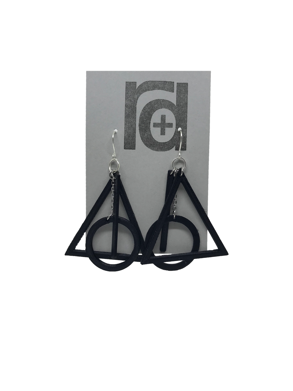 On a grey earring card are two R+D earrings. They are based off of a symbol from a popular book series. There is a black triangle, a circle, and a line that all move independently but come together to make one the master of death.