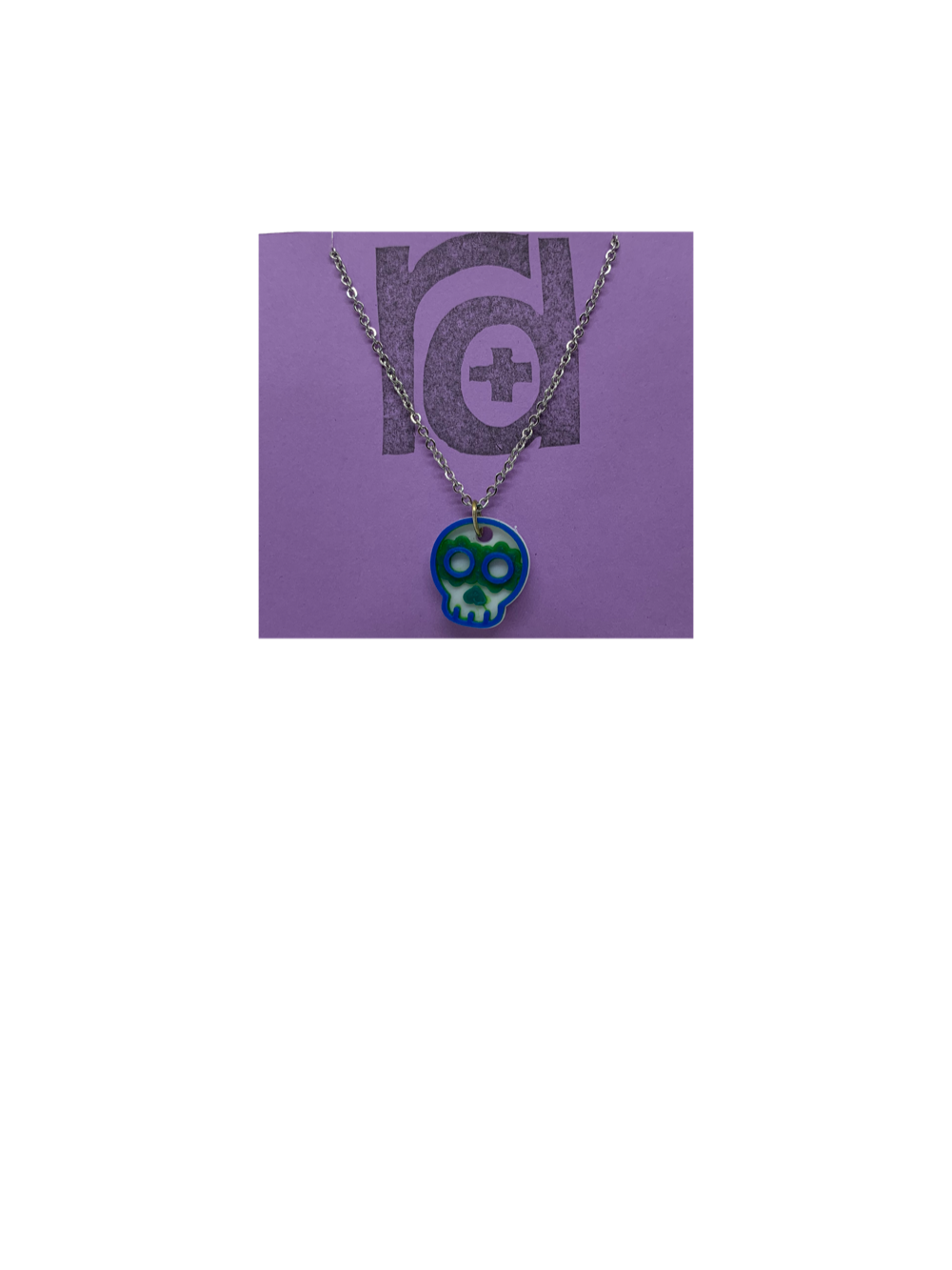 Shown on a light purple R+D earring card is a necklace with a sugar skull pendant. The small pendant is 3D printed in 3 colors: white, green, and blue.