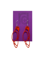 Load image into Gallery viewer, Hanging from a bright purple earring card are two R+D 3D printed earrings. The earrings are red outlines of parrots.