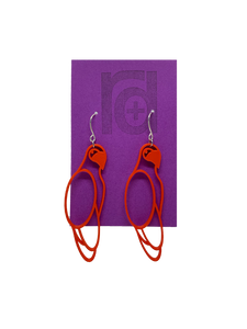 Hanging from a bright purple earring card are two R+D 3D printed earrings. The earrings are red outlines of parrots.