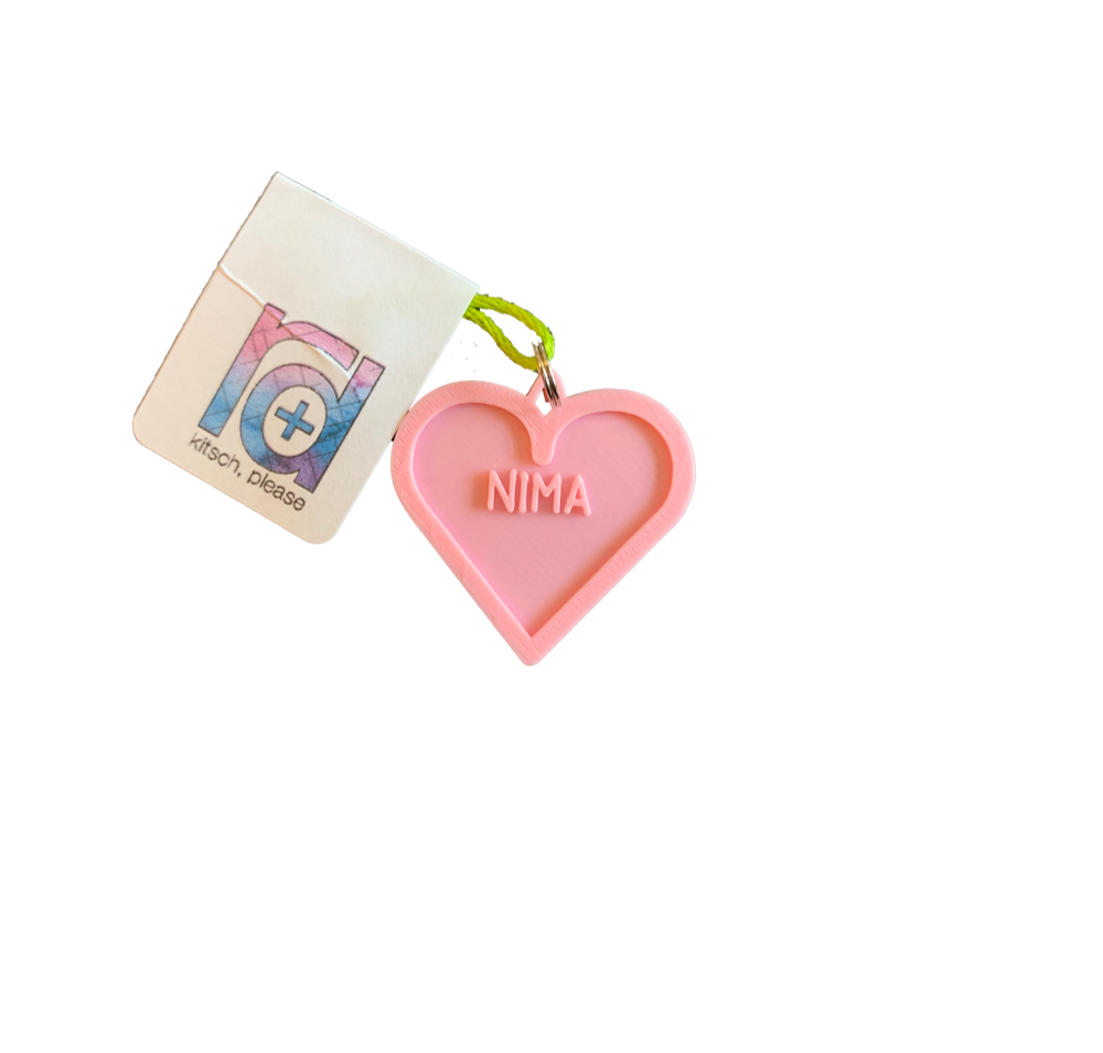 A light pink 3D printed pet tag is in the middle of the photo. It is the shape of a heart with the name NIMA in the middle. This can be customized to 16 other colors and with any name.