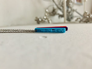 On a white background are three 3D printed pendants. They are each different colors and shaped as long rectangles with names in the center. When worn, they simply look like long hanging rectangles, but from the side, all the names are visible. This one has a teal pendant, a purple pendant, and a red pendant, but from this perspective the  teal pendant is most visible. It reads Douglas.