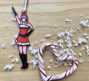 On a wood background with white snow and candy canes shaped into a heart, there is a 3D printed ornament from R+D. The ornament is printed in a plant based filament. It is shaped like Regina George from the movie Mean Girls. She is striking the iconic pose at the beginning of performing Jingle Bell Rock, wearing black gloves and boots and a red outfit with white trim. The entire ornament is covered in glitter to shimmer and shine in the light.