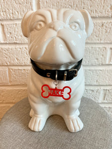 In front of a white brick wall and on a grey cushion is a ceramic bulldog statue. It is wearing a black collar and has a red dog tag. The dog tag is 3D printed in the shape of a dog bone with the name JAKE in the middle. The name can be personalized to any name you would like.