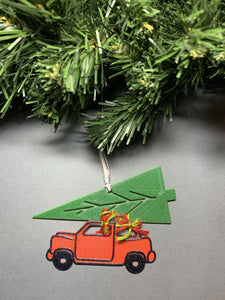 On a grey background and hanging from a green wreath is a R+D 3D printed ornament hanging down. It is shaped as vintage style red car with a big green tree strapped on top. It is held together with red and green bows. The entire ornament is covered in glitter to be able to shimmer and shine in the light.