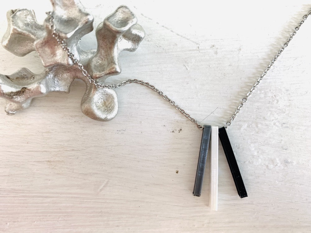 Shown on a white background with an aluminum sculpture on the side. There is a necklace with 3 3D printed pendants. The pendants are long and thin, in silver, white, and black. When turned to the side, names are visible on the pendants.