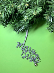 On a bright green background and hanging from a green wreath is a 3D printed R+D ornament. It is a cursive text with a jingle bell and covered in glitter to make it shimmer and shine in the light. This ornament reads, Merry and Bright.