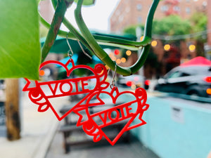In the foreground, hanging off of a green vine are two bright red 3D printed earrings. The earrings are heart shapes with a banner twisted around them and a rose on each side. Across the banner it reads vote, which can be customized with any word.