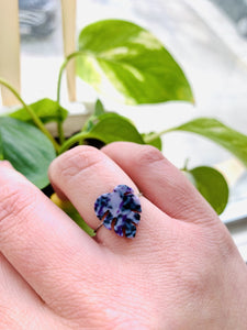 In the foreground is a hand wearing a cast ring in the shape of a monstera leaf. It is cast from recycled 3D prints in hues of purple, black and white. In the background are bright green leafs.
