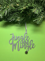 Load image into Gallery viewer, On a bright green background and hanging from a green wreath is a 3D printed R+D ornament. It is a cursive text with a jingle bell and covered in glitter to make it shimmer and shine in the light. This ornament reads, Jingle and Mingle.