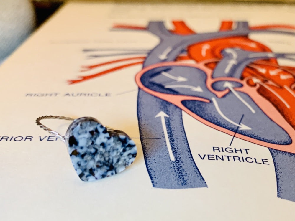 Laying on an old textbook with a drawing of a human heart is a ring that is cast from recycled 3D prints and scraps. The gem on the front is a heart with a smooth surface. It incorporated black, white and silver colors creating a speckled look like granite.