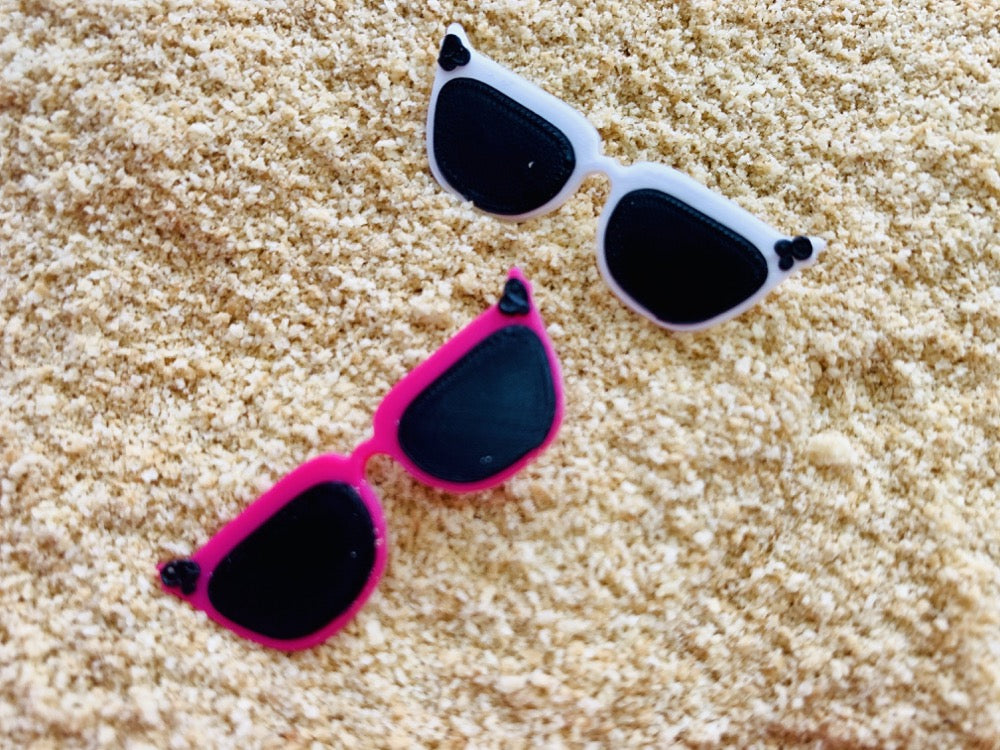 Shown in sand are two 3D printed pins from R+D. They are both shaped like cat eye sunglasses with black lens and black circle accents in the upper corners. The frames are two different colors. One is a bright pure white and the other is a hot pink.