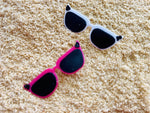 Load image into Gallery viewer, Shown in sand are two 3D printed pins from R+D. They are both shaped like cat eye sunglasses with black lens and black circle accents in the upper corners. The frames are two different colors. One is a bright pure white and the other is a hot pink.