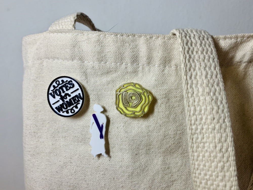 "Shown on a tan tote bag are three R+D 3D printed pins. The first on the left is a white circle with a black outline and words saying ""Votes for Women"". The next is a silhouette of a woman from the 1920s. Aside from the silhouette, there is a purple sash. The third pin is a yellow rose, which was worn in support of the movement. The petals are all outlined in gold and in the center is the number 19 for the 19th amendment."