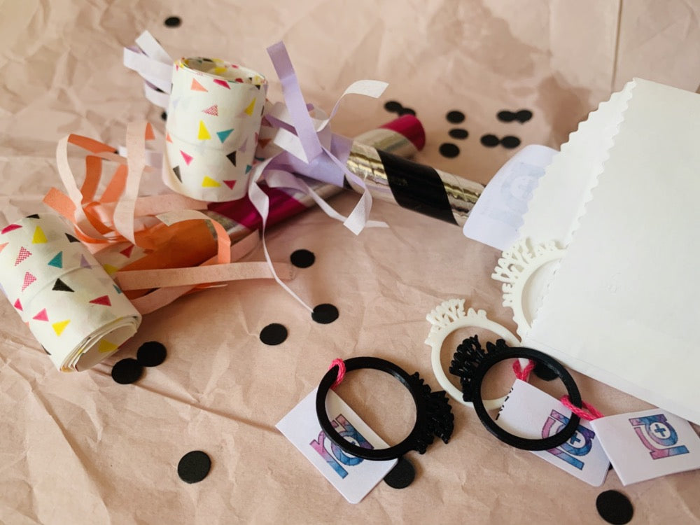 "In this picture there are rings spilling out of a paper envelope. They are black and white 3D printed rings with very small details. The rings each have the words ""Happy New Year"" coming off of the band, similar to a classic New Year's Eve paper crown. In the background, there is black confetti and colorful noise makers."