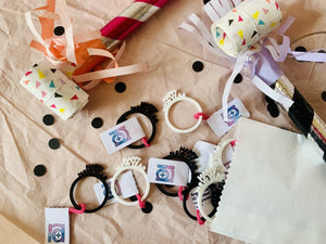 "In this picture there are rings spilling out of a paper envelope. They are black and white 3D printed rings with very small details. The rings each have the words ""Happy New Year"" coming off of the band, similar to a classic New Year's Eve paper crown. Around the rings, there is black confetti and colorful noise makers."