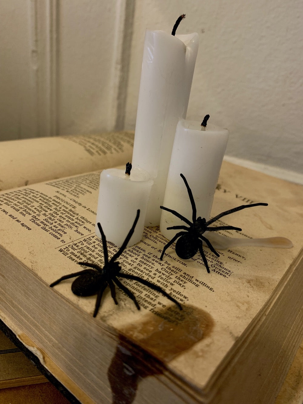 Shown are two black spider earrings that are realistic in their shape. They have long front legs that look like they are searching for their next bit of prey. They are pictured crawling up an old book with candles on top to create a spooky Halloween scene.