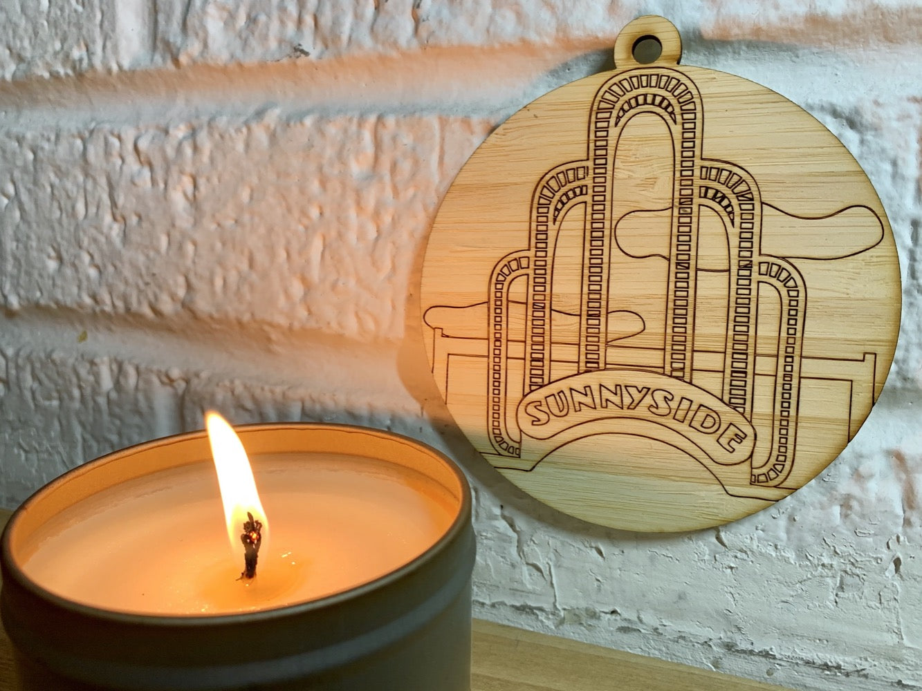 Shown on a white brick wall and next to a candle is a laser cut wall hanging. It is cut from bamboo, a fast growing and sustainable grass. Etched in it a picture of the iconic Sunnyside Arch in the center of the Queens neighborhood. Each piece can be painted like a paint by number or left plain. It can hang from your Christmas Tree or on you wall all year round.