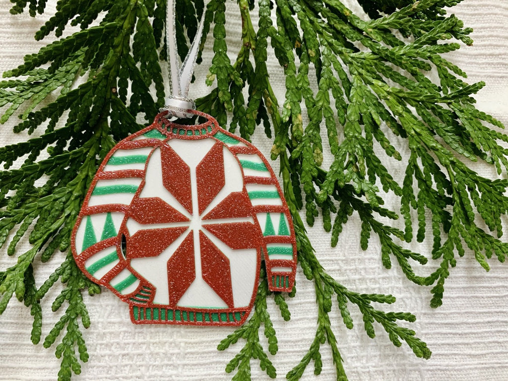 Shown on a white fabric background and with sprigs of evergreen is a R+D 3D printed ornament. It is in the shape of a chunky holiday sweater. It is white with red and green stripes, trees on the sleeves, and a snowflake in the center. The entire ugly sweater ornament is covered in glitter so it will shimmer and shine in the light.
