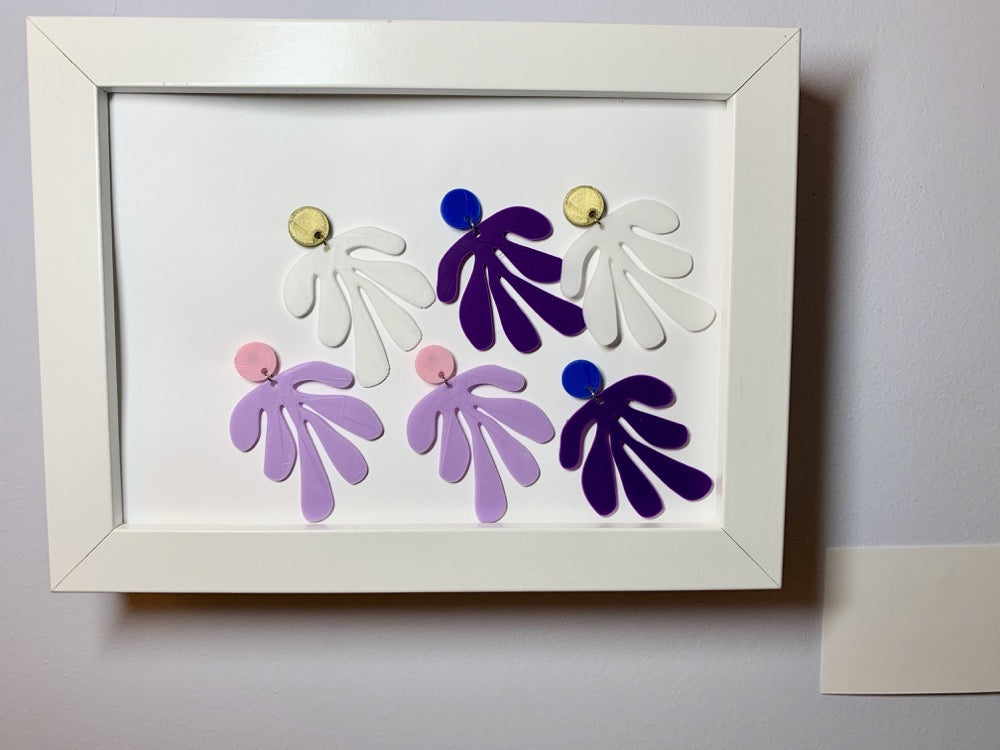 Within a white frame with a small card next to it (suggesting the set up of a museum) are three pairs of earrings. The R+D earrings have a circlar piece at the top linked to an abstract shape based on Matisse's cut out work. The earrings are in gold and white, blue and purple, and light pink and light purple.