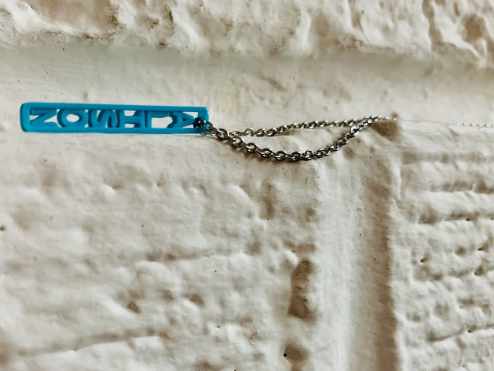 Laying on a white brick ledge is a necklace with a 3D printed pendant. The pendant is teal and have the name ALISON printed in it. These pendants can be personalized to any name, word, or date.
