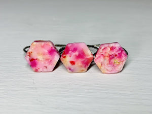 On a white background are three rings side by side. They are each  have a hexagonal shaped charm on the front of the band. The first is a smooth hexagon, the second a faceted hexagon, and the third a bumpy geode. They are cast from recycled 3D prints in red, yellow, orange, hot pink, and white.