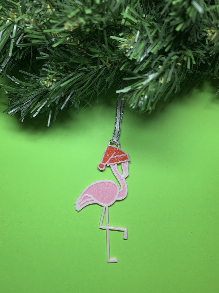 On a bright green background with a wreath above it is a R+D 3D printed ornament. It is a light pink flamingo that has one leg up and is wearing a red santa hat.