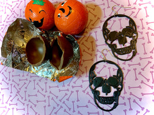Two earrings are shown with pumpkin chocolates for halloween. The earrings are black and in the shape of two large human skulls.