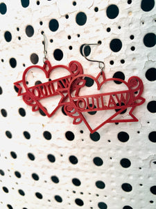Two earrings are hanging off of a background with white paint and holes across it. The earrings are a dark merlot red and shaped like heart tattoos--they are  hearts with a banner twisting around it and two roses. The banner reads outlaw, but can be personalized to any word. They are 3D printed in an eco friendly filament.