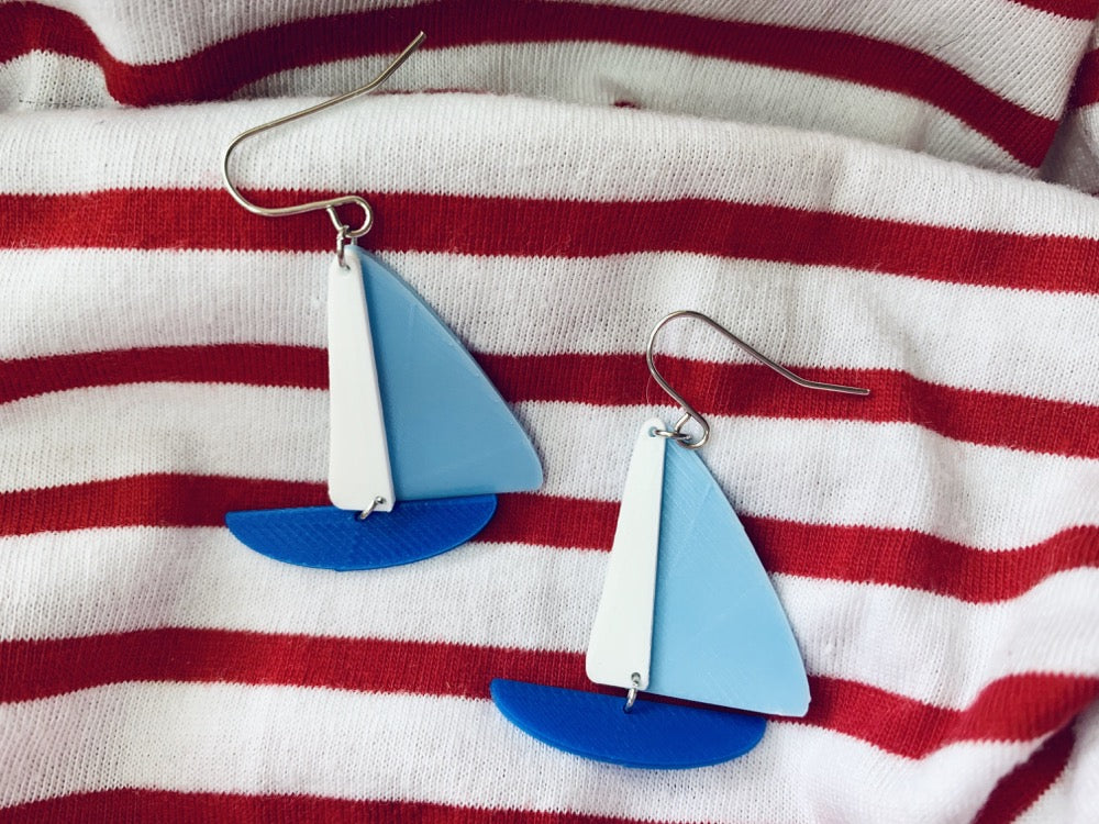 On wrinkled red and white striped fabric, there are two earrings shaped like sailboats. There is a thin white sail, a light blue sail, and a cobalt blue hull.